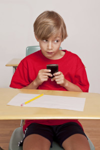A young boy sitting at his desk in class trying to sneak a text on his cell phone as he peeks out of the corner of his eyes looking for the teacher.