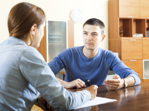 Man questionnaire for social worker or employee at table at home