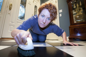 Close up view of a woman scrubbing the floors on her hands and knees.