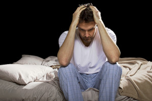 young man holding his head in his hands, unable sleep because of stress