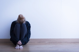 Image of a woman siiting curled up on the ground